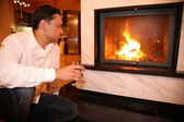 Man and fireplace, focus on glass — Stock Photo