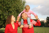 Familia con la hija, que está sentado sobre los hombros del padre — Foto de Stock