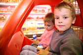 Children in the toy automobile in the supermarket — Stock Photo