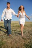 Running couple on meadow — Stock Photo