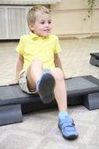 Chico hace ejercicio sentado — Foto de Stock