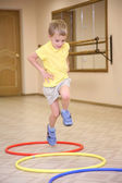 Boy makes exercise ith hoops — Stock Photo