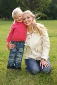 Mother and daughter on the grass — Stock Photo