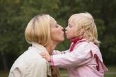 Meisje en moeder kus — Stockfoto