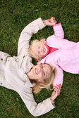 Mother and daughter lie on the grass and look upward 3 — Stock Photo