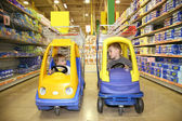 Children in the toy automobiles in the store — Stock Photo