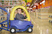 Child in the toy automobile in the supermarket — Stock Photo