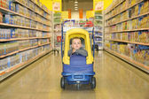 Boy in the toy automobile in the supermarket — Stock Photo