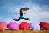 Young woman jumps with the umbrella above the umbrellas — Стоковое фото