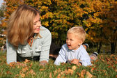 Mother and son lie on the grass at the park in autumn — Stock Photo