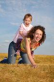 çocuk anne üzerinde oturur — Stok fotoğraf