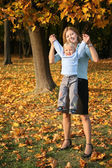 Mother holds son for the hands in the park in autumn — Stock Photo
