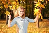 Blue-eyed blond in the park in autumn with yellow leaves — Stock Photo