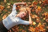 Blue-eyed blond lies among yellow leaves 3 — Stock Photo