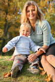 Blue-eyed blond sits with the son in the park in autumn — Stock Photo