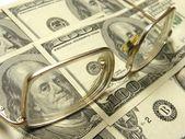 Close-up of dollars and eyeglasses — Stock Photo