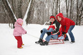 Winter family on sled — Stok fotoğraf