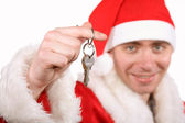 Businessman clothed in costume of Santa holding keys — Stock Photo