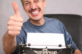 Man after the typewriter shows gesture by the finger — Stockfoto