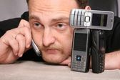 Muž s plnovousem mluví na mobilu, spoléhat se na stůl — Stock fotografie