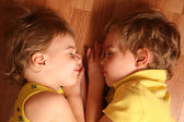 Two children sleep on floor — Stock Photo
