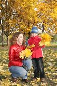 Mother with son in the park in autumn with yello leaves — Stockfoto