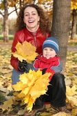 Mother with son in the park in autumn with yellow leaves 2 — Stock Photo