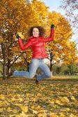 Kırmızı ceketli kız parkta sonbaharda atlar — Stockfoto