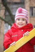 Portrét dívky, která se koná pro dřevěné lišty — Stock fotografie
