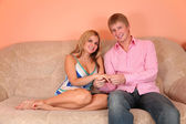 Young couple on sofa in pink room holding ring on finger — Stock Photo