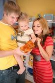 Father and mother hold son on hands in playroom — Stock Photo