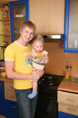 Father holds child on hands on kitchen — Stock Photo