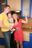 Parents and child on hands in kitchen — Stock Photo