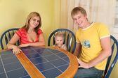 Eltern mit kind sitzen am tisch im zimmer — Stockfoto