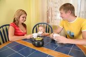 Parents with child drink tea at table in room — Fotografia Stock