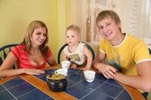 Ouders met kind drinken thee aan tafel in kamer 2 — Stockfoto