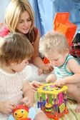 Mother and children in playroom — Stock Photo