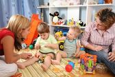 Two mothers play with children in playroom 2 — Stock Photo