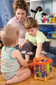 Mother and two children in playroom — Stock Photo