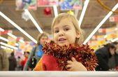 Menina com enfeites luminosos na loja — Fotografia Stock