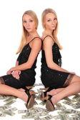 Twin girls sitting on Dollars — Stock Photo