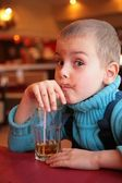 Soiled boy drinks juice from glass through straw — Stock Photo