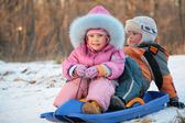 Children sits on plastic sled in park in winter — Stock Photo