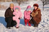 Two mothers with children outdoor in winter — Stock Photo