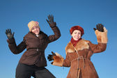 Two young woman posing agains blue sky in winter — Stock Photo
