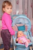 Small girl with the doll in the carriage 2 — Stock Photo