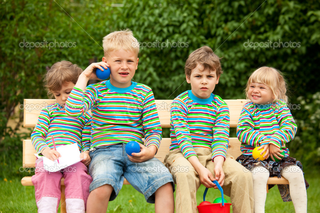 Two boys and two girls on a bench in park. In identical stripe clothes.  Stock Photo #7431162