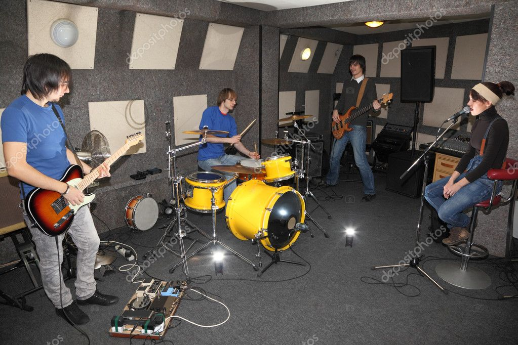 A rock band. vocalist girl, two musicians with electro guitars and one drummer working in studio. flashes in center — Stock Photo #7431332
