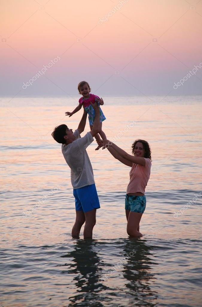 Daddy with mummy and child in sea on sunset — Stock Photo #7433451