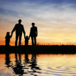 Family of four on sky - Stock Photo